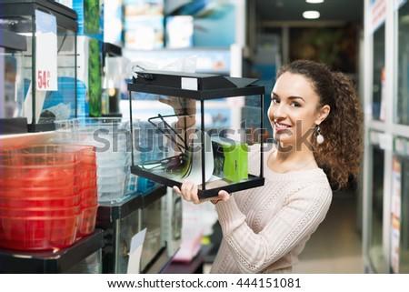 Happy smiling brunette girl choosing domestic aquarium in pet shop - stock photo
