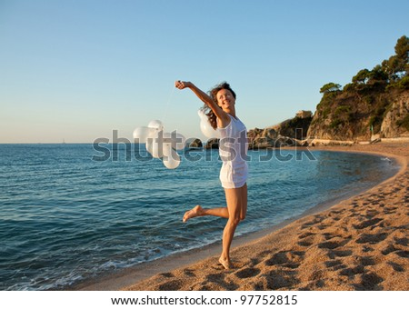 Happy smiling brunette girl with white balloons on sunny beach; summer vacation at Mediterranean Sea - stock photo