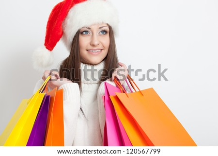 happy smiling brunette woman in santa hat holding shopping bags, copy space