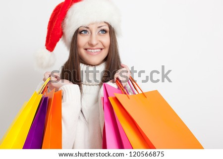 happy smiling brunette woman in santa hat holding shopping bags, copy space for text