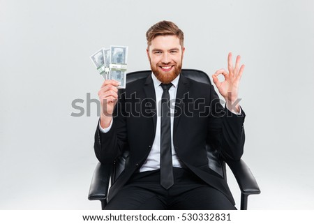 Happy smiling business man in black suit holding money in one hand, showing ok sign and sitting on armchair. Isolated gray background