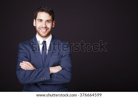 Happy smiling business man with crossed arms on black background - stock photo
