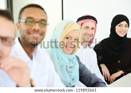 Happy smiling business people sitting in a row - stock photo