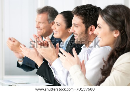 Happy smiling business team clapping hands during a meeting - stock photo