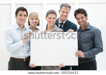 Happy smiling business team holding a blank placard ready for your text or product - stock photo