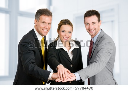 Happy smiling business team holding hands in a heap, good teamwork job - stock photo