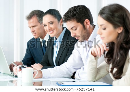 Happy smiling business woman looking at camera while working with colleagues in modern office - stock photo