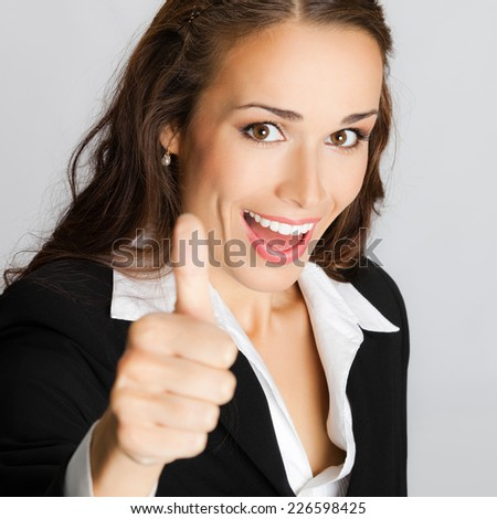 Happy smiling business woman showing thumbs up gesture, against grey background - stock photo