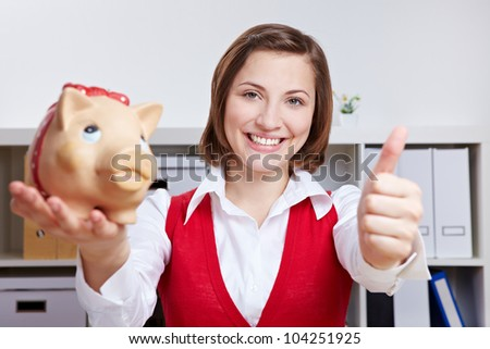 Happy smiling business woman with piggy bank holding thumbs up in office - stock photo