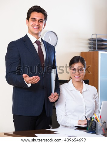 Happy smiling businessman and his young attractive assistant working in modern office 