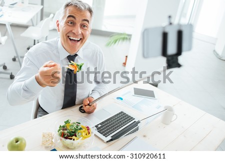Happy smiling businessman at office desk having a lunch break and taking selfies with a selfie stick and a smart phone - stock photo