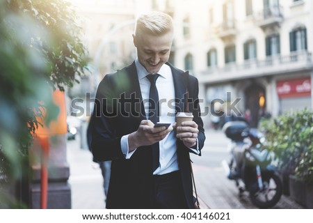 Happy smiling businessman going to the work with coffee cup and using modern smartphone outdoors, successful employer using cellphone while on break outside at sunny day near his office - stock photo