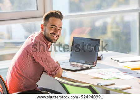Happy smiling businessman looking at camera while sitting at table and working on laptop computer in office interior. Business or freelance concept.