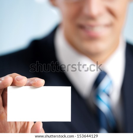 Happy smiling businessman showing blank business card, at office. Focus on hand. - stock photo