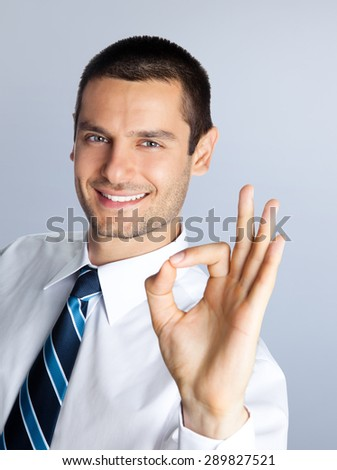 Happy smiling businessman showing okay hand sign gesture, against grey background. Caucasian male model at studio shot. Business and success concept. - stock photo