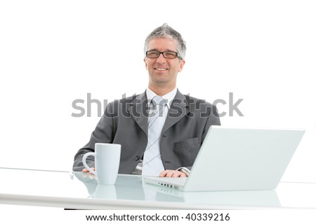 Happy, smiling businessman sitting at office desk with laptop computer and coffee cup on it. Isolated on white background.