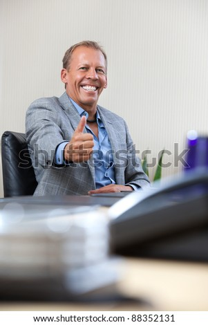 Happy smiling businessman with thumbs up gesture - stock photo