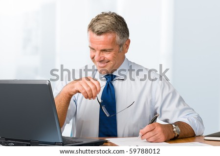Happy smiling businessman working with paperwork and laptop in his modern office