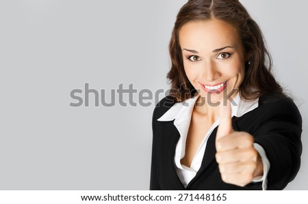 Happy smiling businesswoman showing thumbs up gesture, with blank copyspace area for text or slogan - stock photo