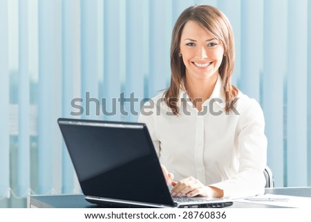 Happy smiling businesswoman with laptop at office - stock photo