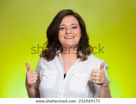 Happy smiling businesswoman with thumbs up gesture, isolated on green background. Positive human emotions, facial expressions, feelings, body language, signs, symbols - stock photo
