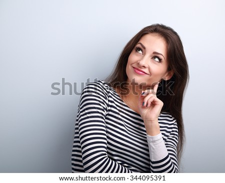 Happy smiling casual woman thinking and looking up on blue background with empty copy space