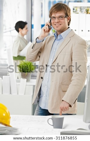 Happy smiling caucasian architect at bright office talking on mobile phone, pointing at table, standing. Suit no tie, looking at camera.