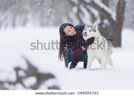 Happy Smiling Caucasian Brunette Woman and Her Husky Dog. Playing Outdoors in Winter White Forest Together. Horizontal Image
