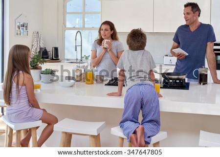 happy smiling caucasian family in the kitchen having breakfast - stock photo