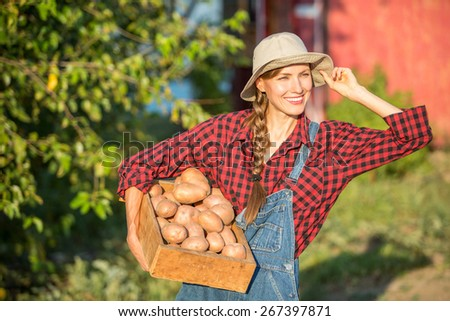 Happy smiling caucasian female farmer or gardener in a hat holding crate with potatoes, fresh vegetables. Agriculture - food production, harvest concept - stock photo