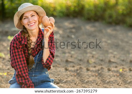 Happy smiling caucasian female farmer or gardener in a hat holding potato, fresh vegetables. Agriculture - food production, harvest concept - stock photo