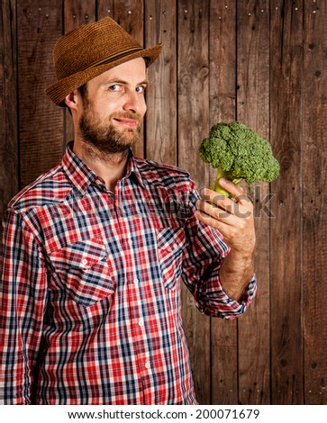 Happy smiling caucasian forty years old farmer or gardener in a hat holding broccoli in hand on rustic vintage planked wood background - agriculture. Food production - vegetables. - stock photo