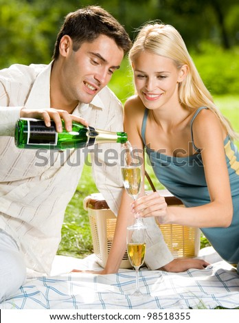 Happy smiling cheerful attractive young couple with champagne at picnic, outdoor