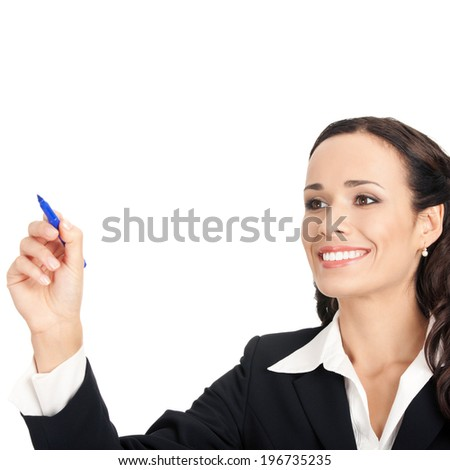 Happy smiling cheerful beautiful young business woman writing or drawing something on screen or transparent glass, by blue marker, isolated over white background
