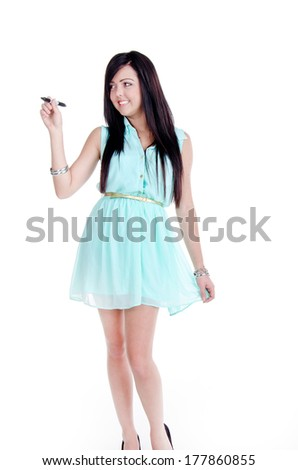 Happy smiling cheerful beautiful young woman writing or drawing something on screen or transparent glass, by blue marker, isolated over white background - stock photo