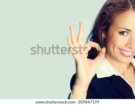 Happy smiling cheerful young brunette businesswoman showing okay gesture, with blank copyspace area for slogan or text message