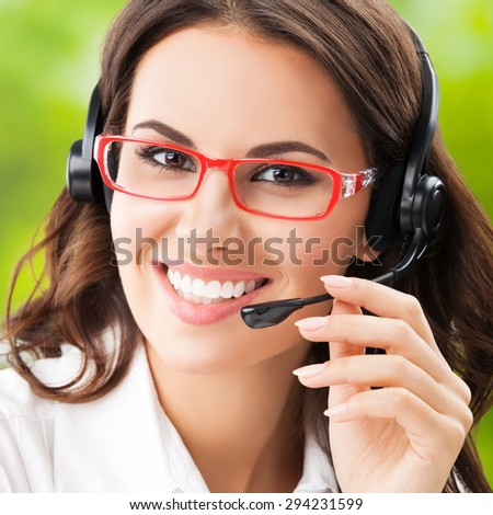 happy smiling cheerful young brunette businesswomen, support phone female operator or call center worker, in headset and glasses. Help and consulting concept.  - stock photo