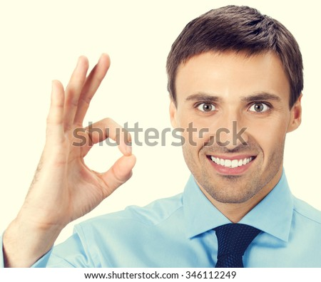 Happy smiling cheerful young business man with okay gesture - stock photo