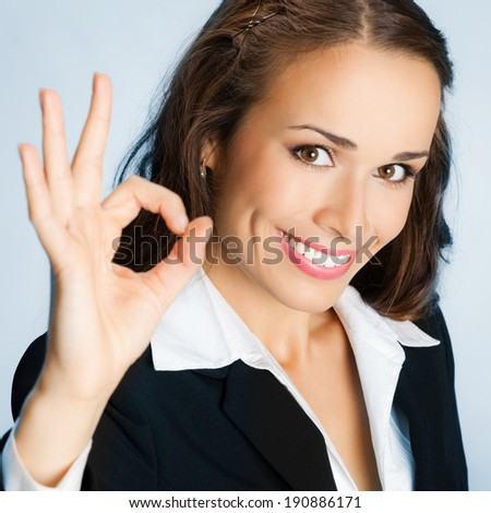 Happy smiling cheerful young business woman with okay gesture, over blue background - stock photo
