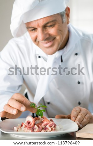 Happy smiling chef garnish a octopus salad with a leaf of persil at restaurant - stock photo