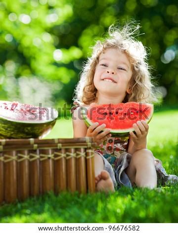 Happy smiling child eating watermelon outdoors in spring park - stock photo