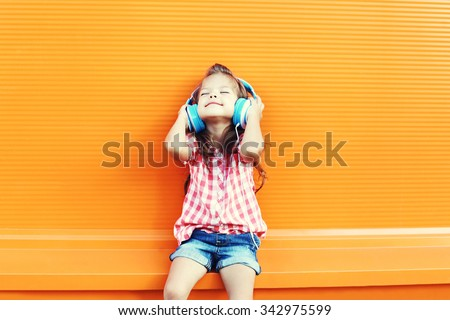 Happy smiling child enjoys listens to music in headphones over orange background - stock photo