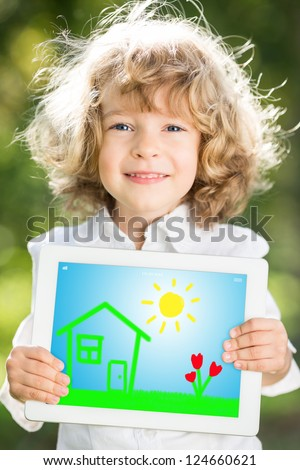 Happy smiling child holding tablet PC against green spring background - stock photo
