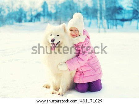 Happy smiling child hugging white Samoyed dog on snow in winter park
