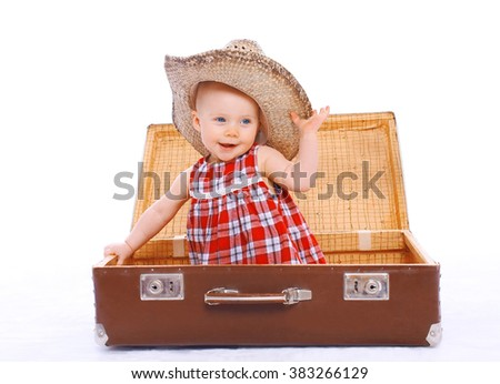 Happy smiling child in straw summer hat sitting on suitcase playing  - stock photo
