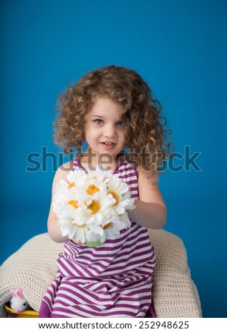 Happy smiling child looking at camera: girl with curly hair holding flowers, Easter or spring theme - stock photo