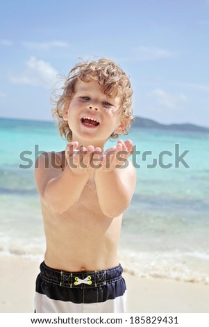 Happy, smiling child on a tropical beach near ocean having fun - stock photo