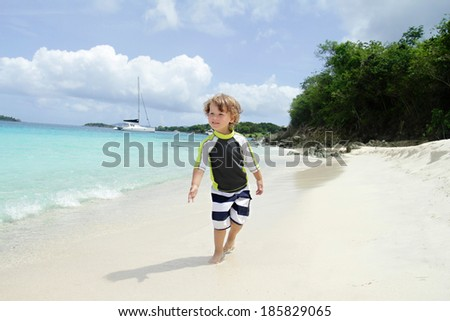 Happy, smiling child on a tropical beach near ocean walking and having fun