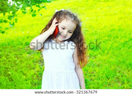 Happy smiling child talking on smartphone in summer day - stock photo