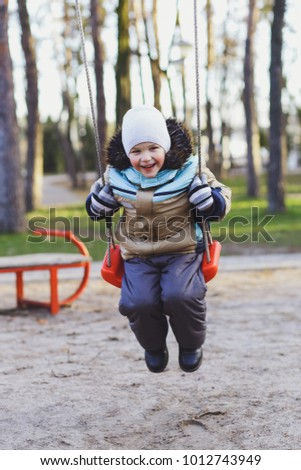 Happy, smiling children, kids, the boy is riding on a swing in the park.